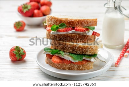 Sandwiches with brie or Camembert cheese, strawberries and mint. Delicious breakfast. Selective focus