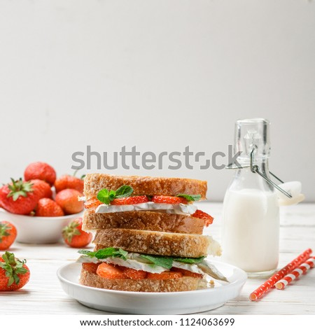 Sandwiches with brie or Camembert cheese, strawberries and mint. Delicious breakfast. Selective focus. square picture, copy space