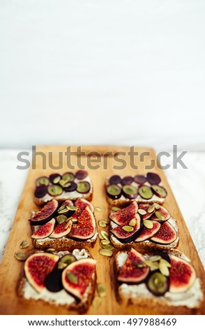 sandwiches with cheese grapes figs on wood #497988469