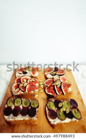 sandwiches with cheese grapes figs on wood #497988493