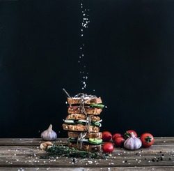 Sandwiches with smoked meat, cucumber and herbs tied with a rope, placed one over another. Salt is being strewed on them from above on them