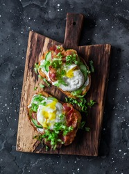 Sandwiches with smoked salmon, green salad and boiled egg on the dark background. Delicious breakfast, snack