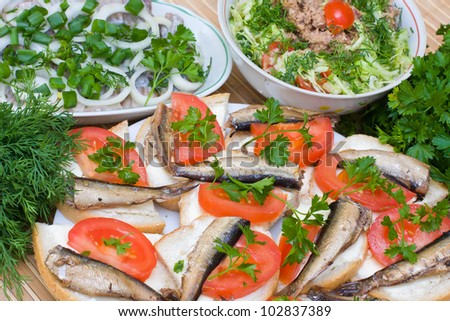 Sandwiches with sprats and tomatoes on a plate