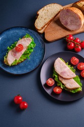 Sandwiches with turkey ham meat, green salad and fresh cherry tomatoes slices on black and blue plate near to ingredients on cutting board, blue minimal background, angle view macro