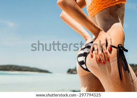 Sandy ass of a young beautiful sporty woman in striped black and white bikini on the tropical ocean shore background. Outdoor lifestyle picture on a hot sunny summer day.
