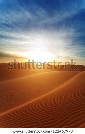 Sandy barkhans in the evening. The sun with beams in the desert. - stock photo