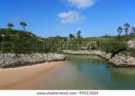 Sandy beach and rocky coastline under blue sky in Northern Spain