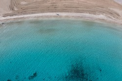 Sandy beach, clear blue turquoise color sea water aerial drone top view. Man walking alone on Platia ammos beach Ano Koufonisi island, Small Cyclades. Cleaning machine traces on the sand
