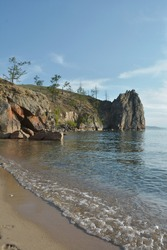 sandy beach in the bay, surrounded by large ancient rocks in sunny weather