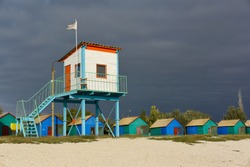 Sandy beach landscape. Closeup a construction with a lifeguard tower and a row of wooden colorful one-story cabins for vacationers against a dark blue, pre-thunderstorm sky.Nobody. Resting on the sea.