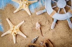 Sandy beach old blue wood background on decorative steering wheel with starfish, seashells