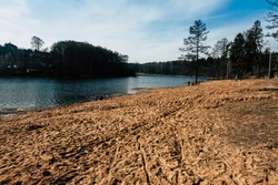 Sandy beach on the river. People walking and resting on the sandy Bank of the river. Natural landscape of sandy shore of a forest river against the blue sky and dark trees