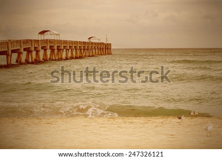 stock-photo-sandy-beach-scene-with-an-empty-pier-on-a-stormy-day-with-instagram-style-filter-applied-while-247326121.jpg