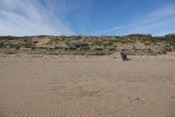 sandy beach with a dune in the background. The sand dune has vegetation. At the foot of the dune, there is a bunker which is buried. The sky is blue with a few clouds