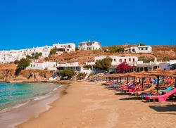 sandy beach with colored sunbeds and thatched umbrellas in the Bay of Greek island.
