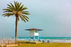 Sandy beach with palm tree and life guard tower in Larnaca, Cyprus