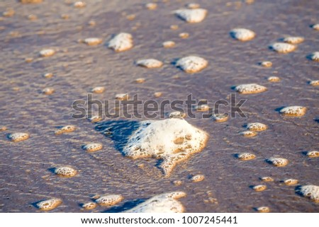 sandy beach with pebble and spray of the surf #1007245441