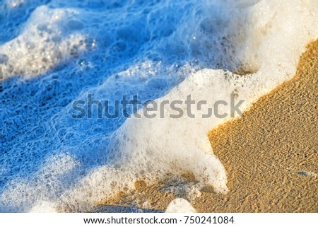 sandy beach with spray of the surf #750241084