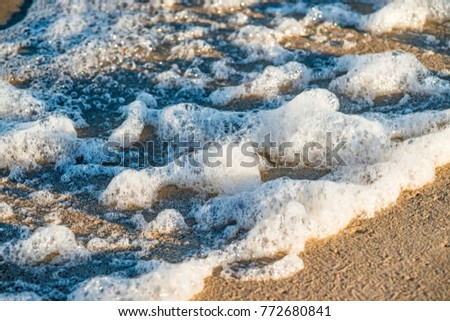 sandy beach with spray of the surf #772680841
