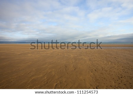 sandy beach with the tide out at sunset in north wales