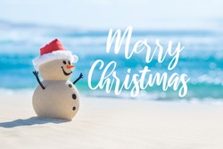 Sandy Christmas Snowman is celebrating Christmas on a beautiful beach with Merry Christmas wishes in the background