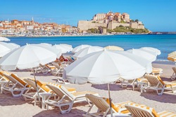 Sandy Corsican beach and amazing azure sea with an ancient citadel of Calvi in background. Historical touristic place.