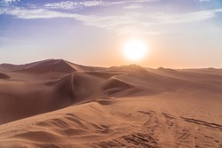 Sandy desert at sunset. Dry, hot sand deserted vibes. Travel, holiday, explore scenic shot, with sand ripples, sun setting and footprints. Tourism shot in Huacachina, Peru. Epic, dramatic shot.