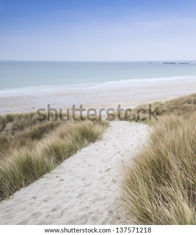 Sandy path leads down through dunes to beautiful golden beach at sunset