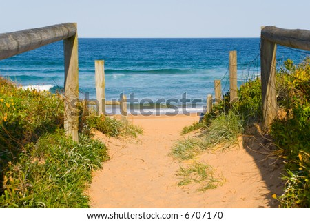 sandy path leads down to the beach and ocean on a perfect blue sky sunny day