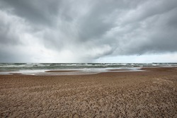 Sandy shore of the Baltic sea under the dramatic clouds after thunderstorm. Ventspils, Latvia. Epic seascape. Cyclone, gale, storm, rough weather, meteorology, climate change, natural phenomenon
