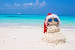 Sandy snowman with red Santa Hat on white Caribbean beach