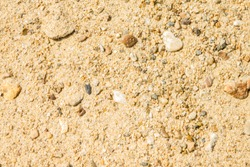 Sandy texture, coast, river bank. Large sand with small stones, bright sunlight. Rest, summer, beach.