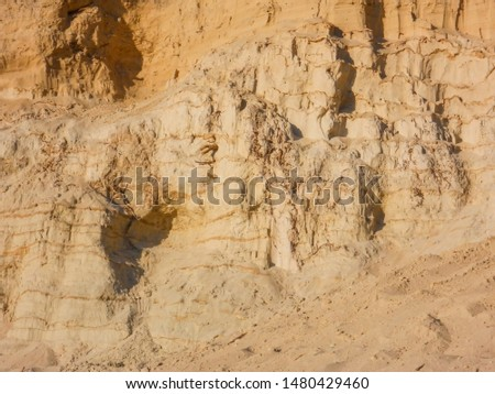 sandy wall background made by layers of yellow sand with different densities in a sand pit imitation of rock. selective focus #1480429460