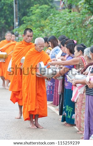 SANGKHLABURI , THAILAND - OCT. 3: An unidentified woman Gives food  to a monk.Thai traditional, people will make merit making by give food to monk on October 3, 2011 in Sangklaburi, Thailand.