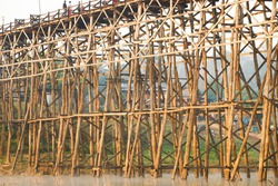 Sangklaburi or Myanmar tall wooden bridge on Songaria River, A International Famous tourist destination with beautiful view and local traditional culture. Architecture of Wood bridge connect two world