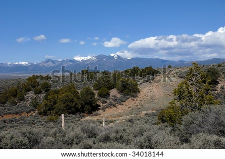 Sangre De Cristo mountains have snow caps and low hanging clouds.  Small dirt road curves into the foothills and rustic fence follows.  Historic town of Taos sprawls at foot of mountain.