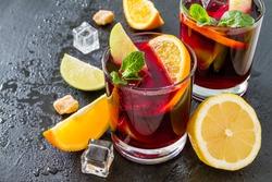 Sangria in glasses with ingredients - orange, lemon and lime slices, sugar, dark stone background