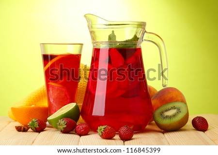 sangria in jar and glass with fruits, on wooden table, on green background