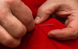 sanior old man or woman Sews with a needle and thread at home. Fingers hands of the seamstress is using a needle and red thread to sew cloth close-up
