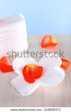 Sanitary pads and rose petals on wooden table on light blue background