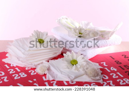Sanitary pads and white flowers on red calendar on pink background