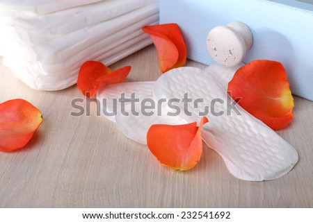 Sanitary pads in box and rose petals on light grey background