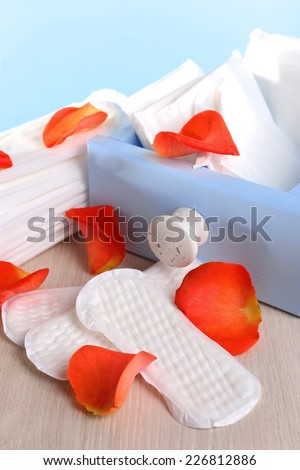 Sanitary pads in box and rose petals on wooden table on light blue background