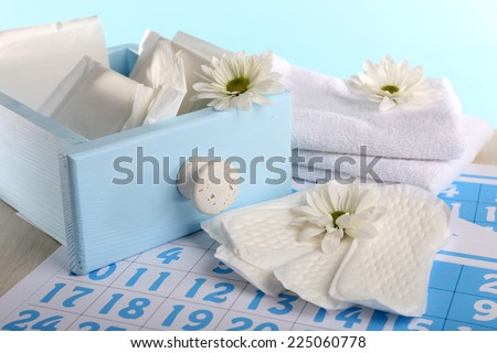 Sanitary pads in box and sanitary pads and white flowers on blue calendar on light blue background