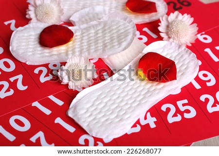 Sanitary pads, white Berbers and rose petals on red calendar background