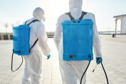 Sanitization and disinfection of the city due to the emergence of the Covid19 virus. Specialized team in protective suits and masks with backpack of pressurized spray disinfectant water. Rear view