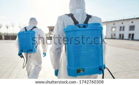 Sanitization and disinfection of the city due to the emergence of the Covid19 virus. Specialized team in protective suits and masks with backpack of pressurized spray disinfectant. Rear view Foto stock ©