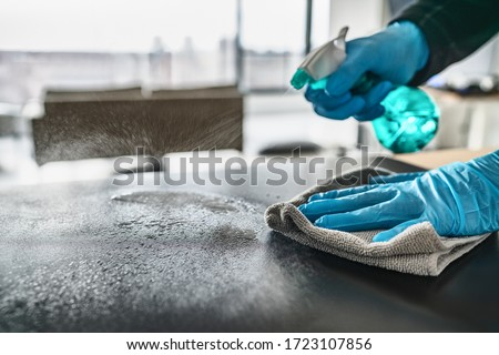 Sanitizing surfaces cleaning home kitchen table with disinfectant spray bottle washing surface with towel and gloves. COVID-19 prevention sanitizing inside.