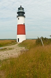 Sankaty head lighthouse on the northeast corner of the barrier island,nantucket, sitting in a grassy field on a clear day
