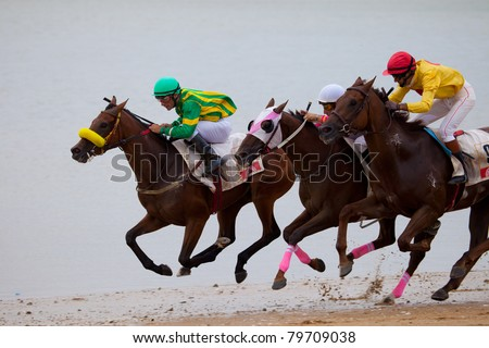 SANLUCAR DE BARRAMEDA, CADIZ, SPAIN - AUGUST 07: Unknown riders of the horses races of the beach of Sanlucar de Barrameda on August 07, 2010 in Sanlucar de Barrameda, Cadiz, Spain.